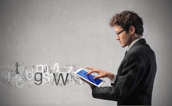 Mann im Anzug sucht auf seinem iPad nach Infos.
